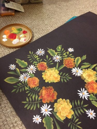 Yellow and orange marigolds, daisies and assorted leaves painted on black paper.