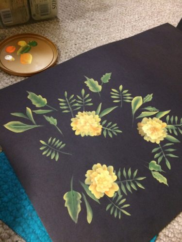 Snapshot of yellow marigolds and various leaves painted on black paper.