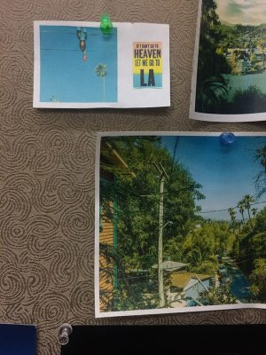 "Photo of a cubicle wall with three printed out images on it: two views of the Los Angeles area around Dodger stadium and one small piece of paper with a picture of a palm tree and a small gradient rectangle that says ""If I Can't Go To Heaven Let Me Go To LA"""