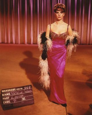 "Natalie Wood in a pink satin gown, with a feather boa. She's standing on an empty stage, next to a blackboard that reads ""Wardrobe Prod No 869,"" along with other details."