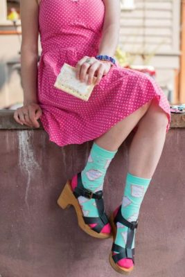 A model is shown from the neck down. They're wearing a bright pink summer dress, with short blue socks covered in a pop tart pattern. The model is casually holding a pop tart that matches the ones on the socks.