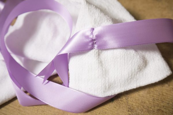 A white sock with a light purple ribbon hand sewn to the cuff. The stitches are a little rough, but look serviceable.