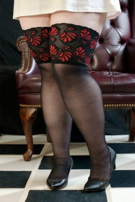 A model wearing sheer black stockings with a cuff off intricate black and red brocade.