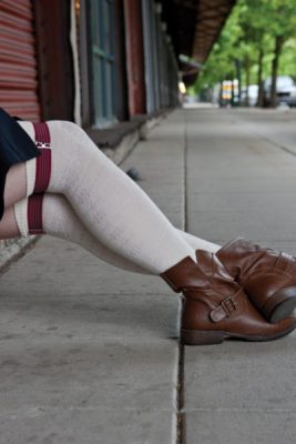 A person sits on a low ledge, their legs crossed and stretched in front of them. They're wearing a skirt and over the knee, off white socks with a floral knockout pattern. The socks are held up by simple burgundy sock garters.