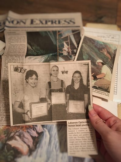 A hand with long nails holding a newspaper clipping of three teens showing off certificates of achievement. In the background are more newspaper clippings and photos of the mural in progress.