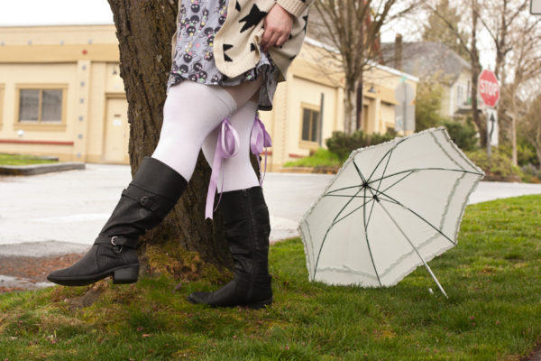 A person is slightly lifting the hem of their skirt as they kick a leg forward, wearing tall white socks with light purple ribbons on the back and mid-calf black boots. It's been rainy, the pavement is wet and there is a frilly umbrella discarded in the background.